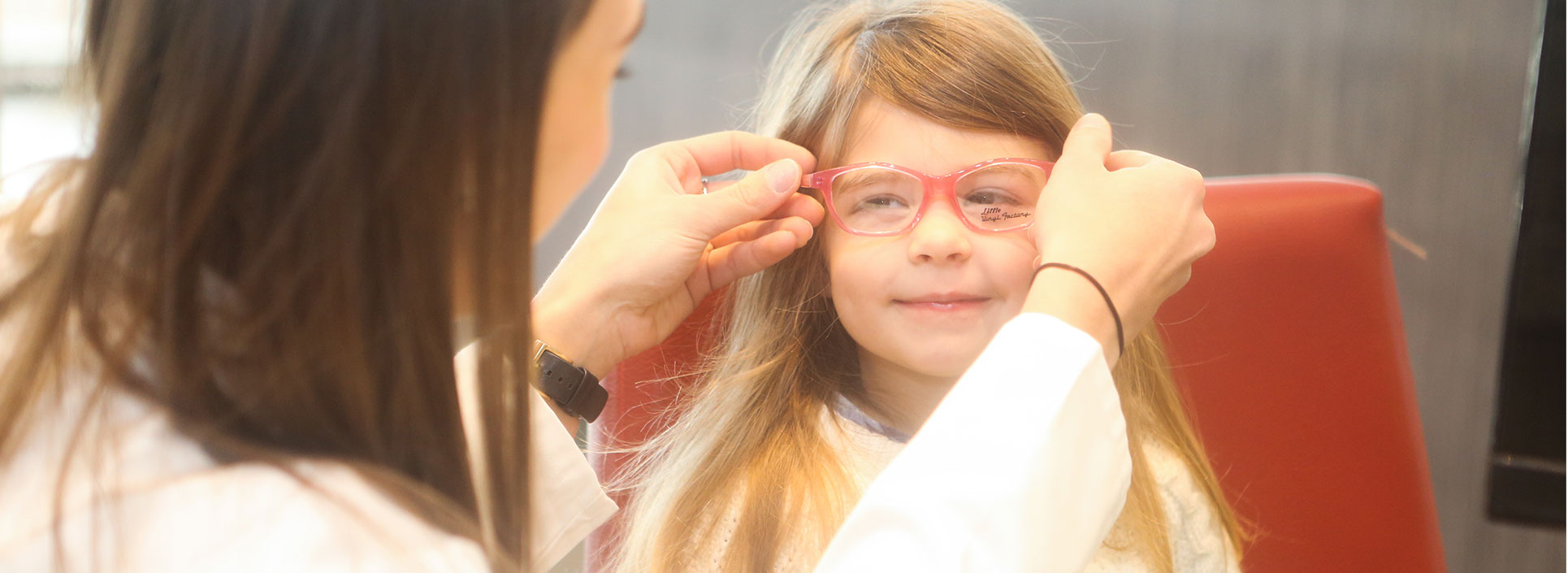 An employee of Roswell Eye Clinic placing a pair of glasses on young girl's smiling face.