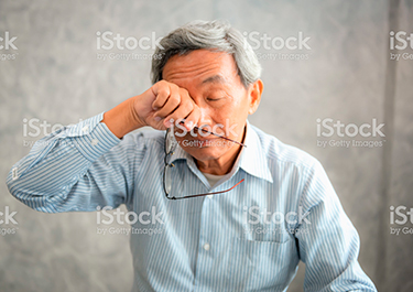 Asian man rubbing his eyes, holding his glasses.