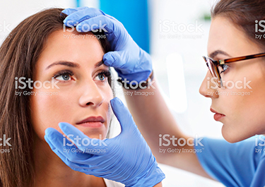 A lady nurse, wearing gloves, examining the eyes of a female patient.