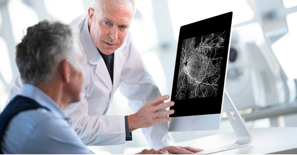 A doctor pointing to a screen of a medical view of the nerves of an eye to a patient.