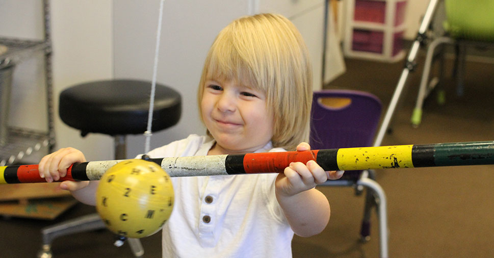 A smiling young boy during a vision therapy session, holidng a bat up near a ball that is hanging from the ceiling.