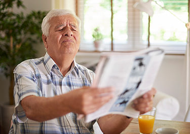 Man with poor eye sight holding newspaper squinting.